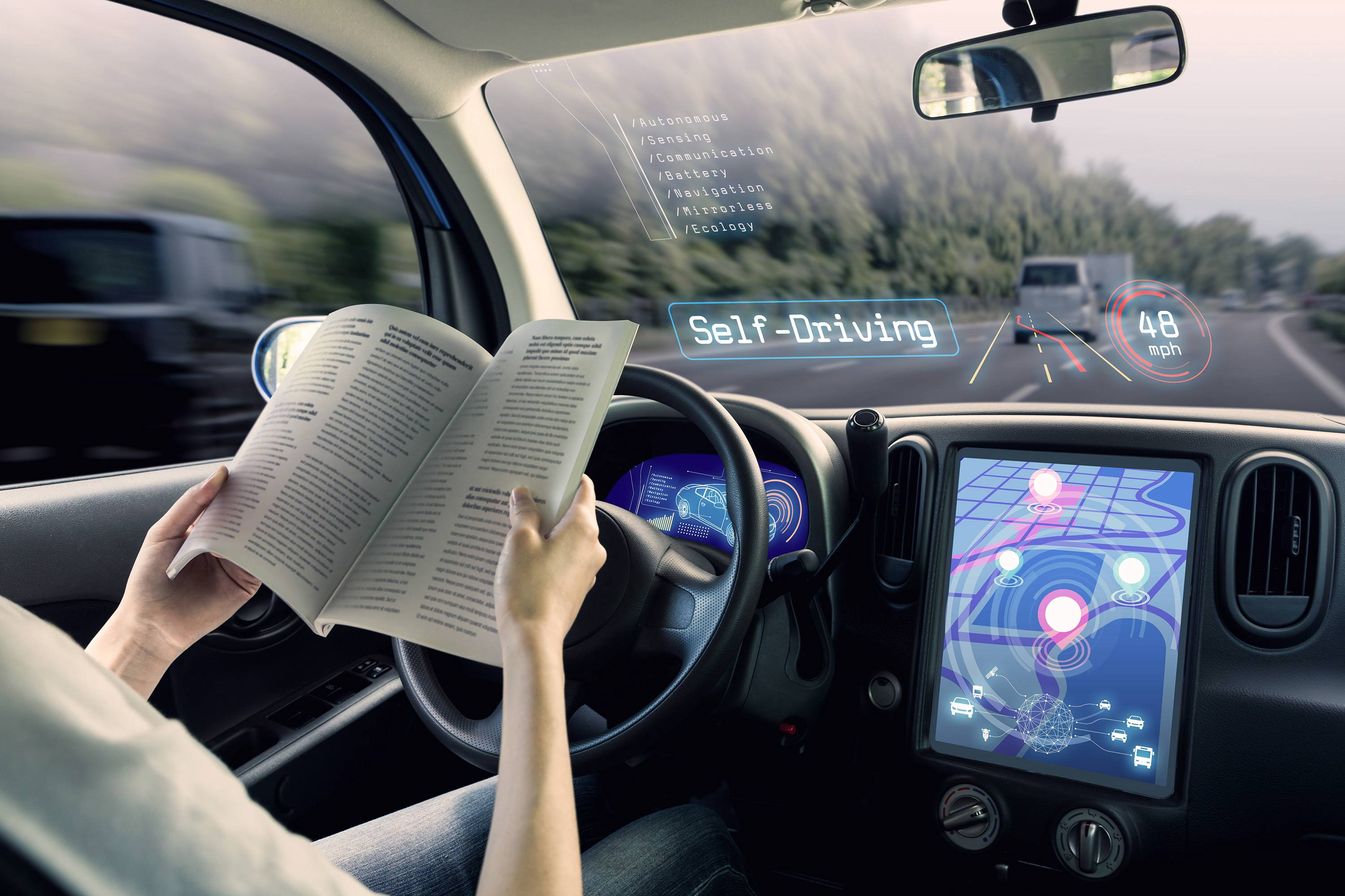 Interior of self-driving car with person reading while at the steering wheel